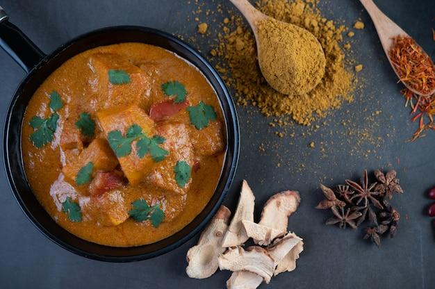 Massaman curry in einer pfanne mit gewürzen auf dem zementboden