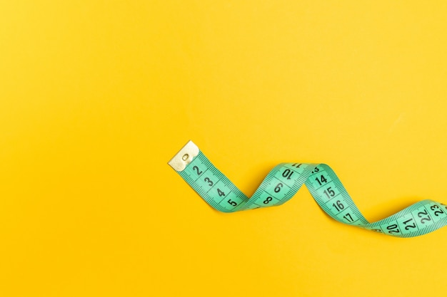 Maßband auf gelbem grund. diät, abnehmen, fettleibigkeit konzept.