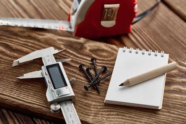Maßband, bremssattel und notizbuch, holztisch. professionelle instrumenten-, tischler- oder baumaschinenausrüstung, holzbearbeitungswerkzeuge