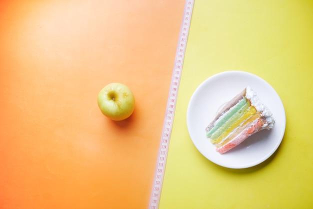 Maßband grüner apfel und ein backkuchen auf farbigem hintergrund