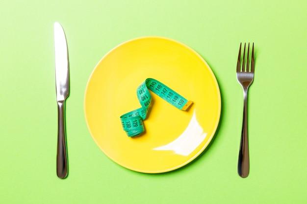 Maßband in einer platte mit gabel und messer beidseitig auf grün