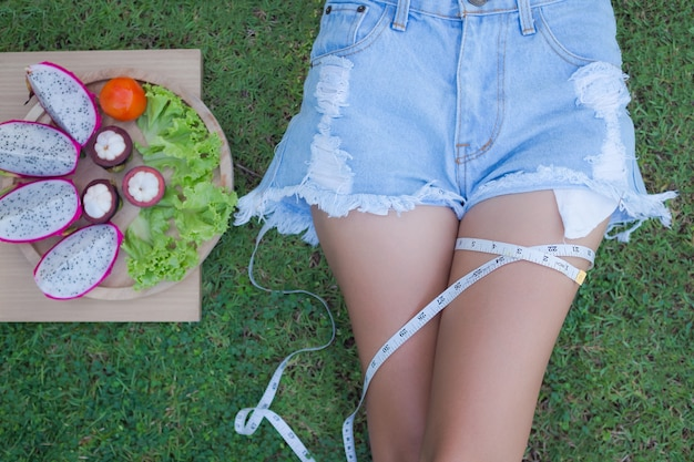 Maßband mit frauenbein auf gras.
