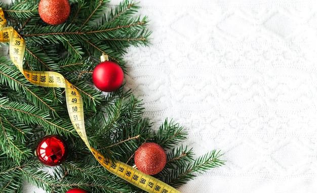 Maßband mit weihnachtsdekoration lokalisiert auf weißem gestricktem hintergrund. horizontales foto