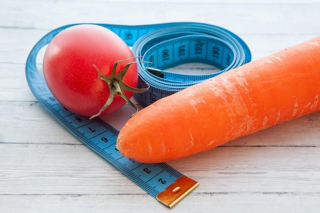 Maßband, saftige tomate und karotte, das konzept der gesunden ernährung und das abnehmen