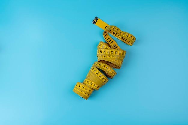 Maßband von schneider mit indikatoren in form von zentimetern. gelb gerolltes maßband auf blauem hintergrund isoliert. . gerolltes zentimeterlineal von gelber farbe, nahaufnahme