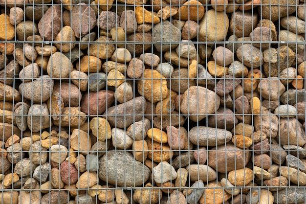 Masse der bunten kopfsteine, die hinter metallmasche legen