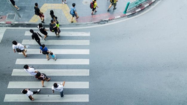 Masse der leute gehen auf straßenfußgängerkreuzung in der stadtstraße