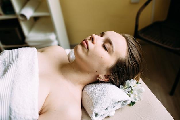 Masseur bei massage im gesicht einer frau im spa