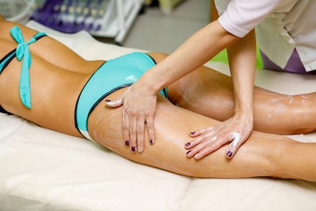 Masseur, der creme auf den oberschenkel der frau aufträgt. massage im spa-salon