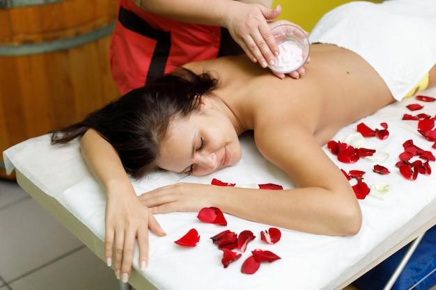 Masseur, der creme auf den rücken der frau aufträgt. massage im spa-salon