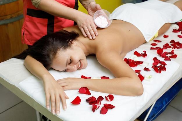 Masseur, der creme auf den rücken der frau aufträgt. rosenblätter. massage im spa-salon