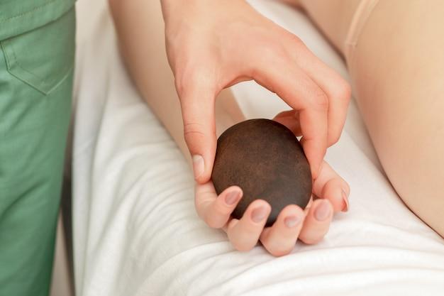 Masseur legt dem patienten einen massagestein in die hand.