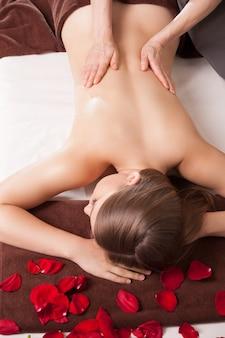 Masseur macht massage am körper der frau im spa-salon. schönheitsbehandlungskonzept.