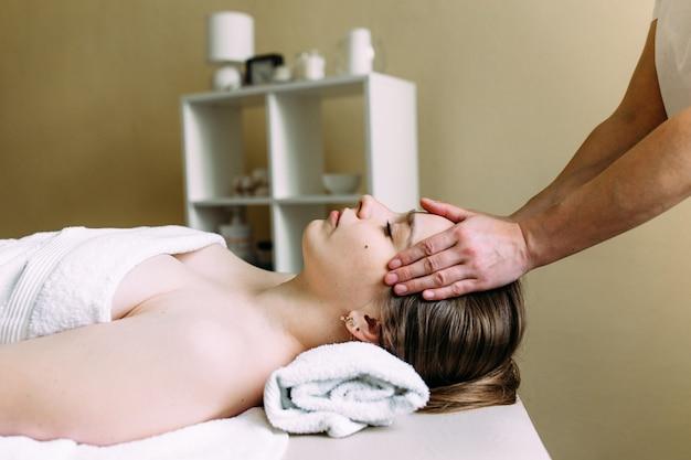 Masseur macht massage auf dem gesicht einer frau im spa