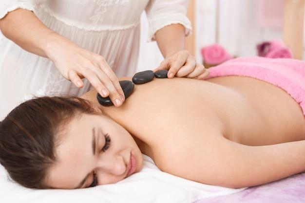 Masseur macht massage mit heißen steinen auf frau zurück