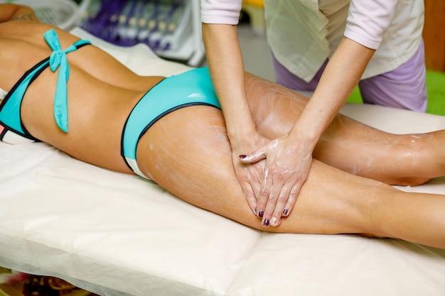 Masseur trägt creme auf oberschenkel und gesäß der frau auf. massage im spa-salon