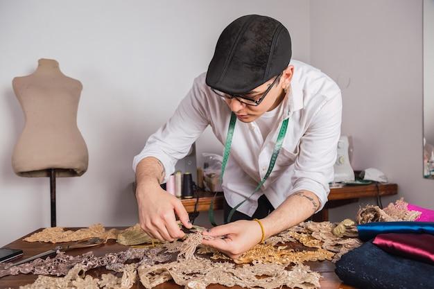 Maßgeschneidertes designer-arbeitsplatzkonzept - porträt von schneiderspitzendeckchen zum aufnähen des kleides.