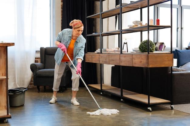 Massive reinigungssitzung. aktive fitte erwachsene frau in hellem outfit, die sorgfältig den boden mit langem mopp wäscht