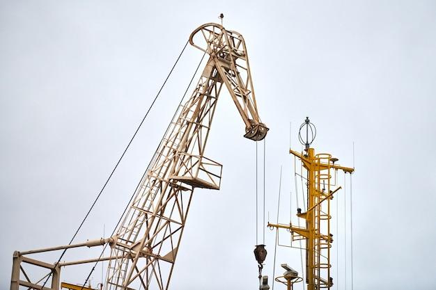 Massiver hafenkran im hafen. schwerlast-hafenkran im seehafen, frachtcontainerhof, containerschiffsterminal. wirtschaft und handel, logistik