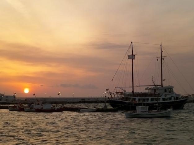Mast des segelboots gegen schönen sonnenunterganghimmel über dem alten hafen von mykonos, griechenland