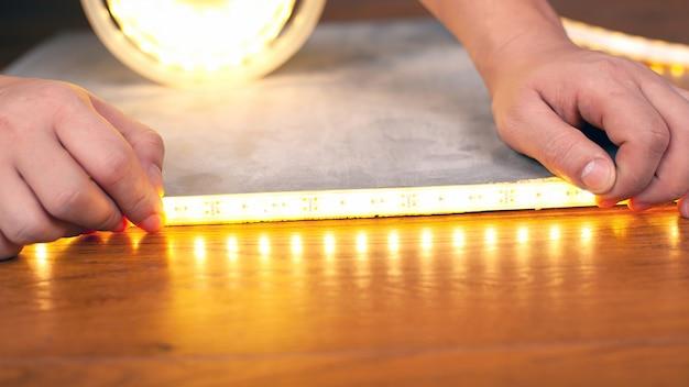 Master installiert eine leuchtende led-streifen-nahaufnahme, hände kleben klebeband auf eine holzoberfläche.