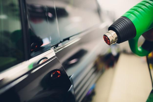 Master installiert tönungsfolie für auto mit haartrockner. konzeptschutzauto
