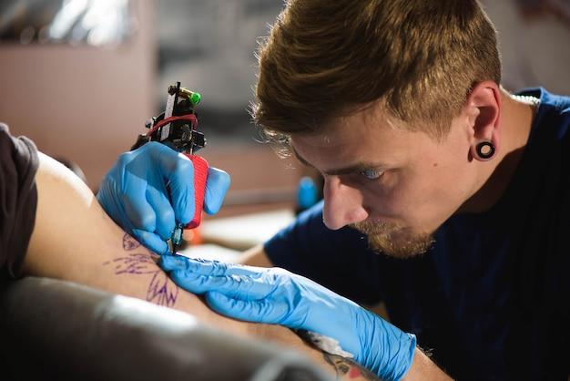 Master tattoo zeichnet die schwarze farbe auf das tattoo des kunden.