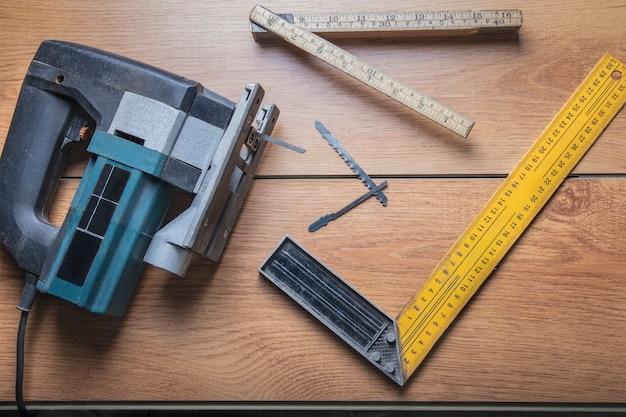 Master tools lineal ersatznagelfeilen und elektrische stichsäge auf dem laminat in der werkstatt