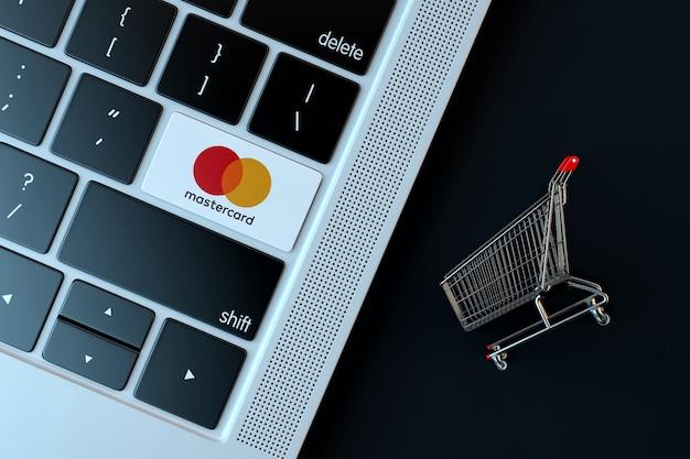 Mastercard-logo auf laptop-tastatur und miniatur-einkaufswagen