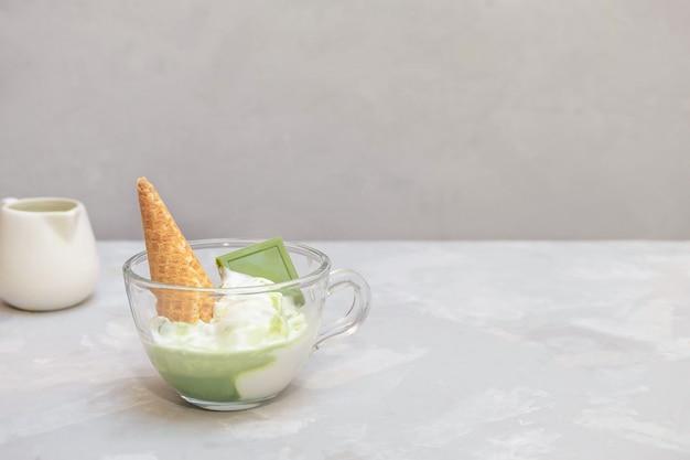 Matcha-affogato-rezept mit vanilleeis und gesundem matcha-grüntee in einer glasschale auf grauem tisch