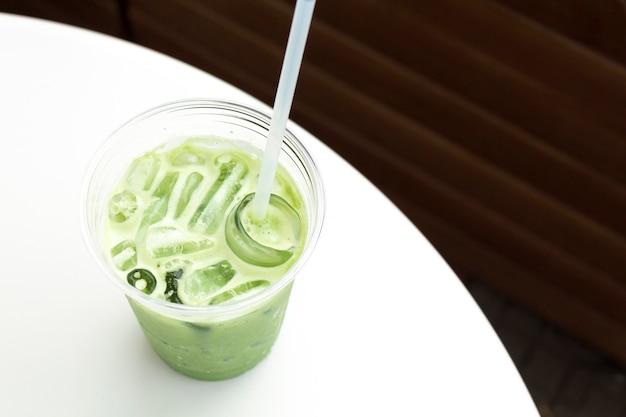 Matcha-eis-grüntee-latte in tasse zum mitnehmen auf weißem tisch auf holzhintergrund