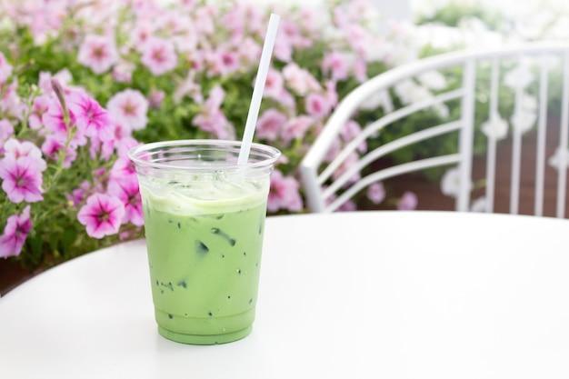 Matcha-eis-grüntee-latte in tasse zum mitnehmen auf weißem tisch gegen blütenblumen against