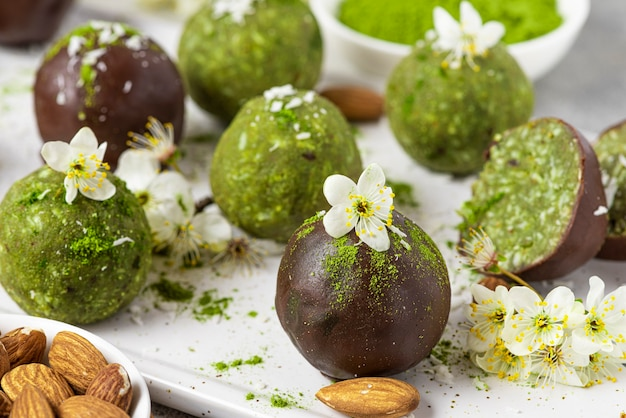 Matcha energy bites oder bällchen in schokoladenglasur mit blumen. rohes veganes gesundes snackdessert. nahansicht