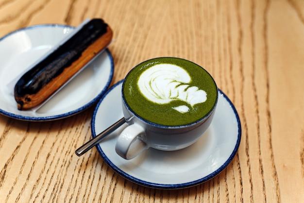 Matcha grün in einem weißen becher auf einem holztisch in einem café neben einem süßen dessert. schokoladen-eclair zum frühstück