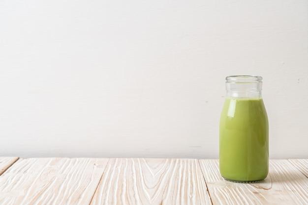 Matcha grüner tee mit milch in der flasche auf holztisch