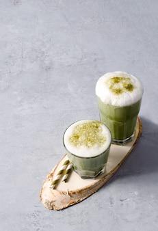 Matcha grüner tee und kaffee latte mit schaum auf einem holzständer und einem betonhintergrund mit kopierraum