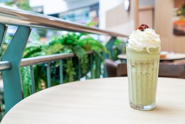 Matcha grüntee latte gemischt mit schlagsahne und roten bohnen im café und restaurant des coffeeshops