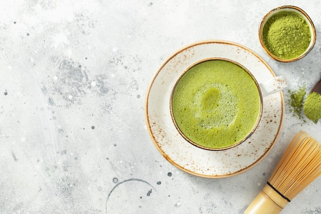 Matcha grüntee latte in einer tasse mit sahne auf leichtem beton