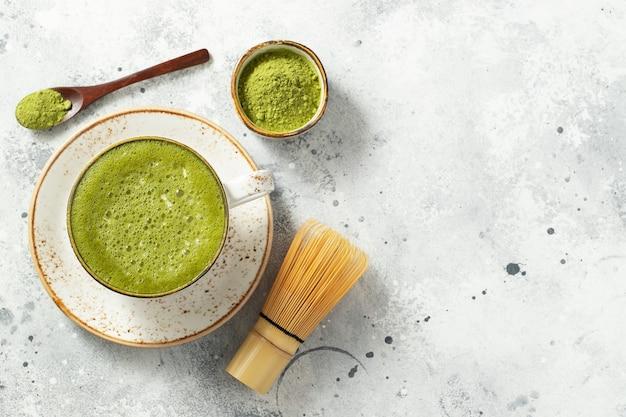 Matcha grüntee latte in einer tasse mit sahne.