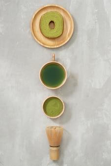 Matcha grüntee latte in einer tasse und teezeremonie utensilien mit deutschem kuchen. platz kopieren