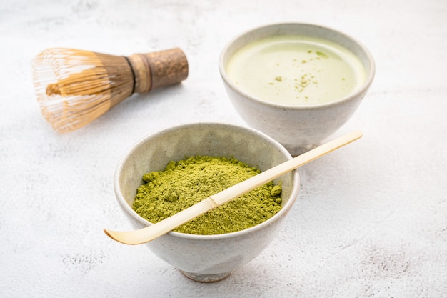 Matcha-grüntee-pulver mit bambus-matcha-schneebesen-bürstenaufbau auf weißem betonhintergrund