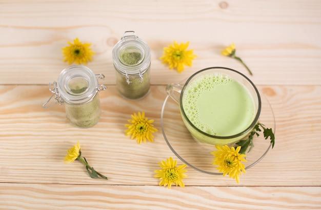 Matcha latte in einer tasse mit matcha-pulver
