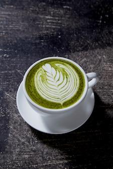 Matcha-tee latte auf schwarzer tabelle