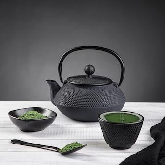 Matcha-teepulver und teezubehör auf heller basis auf grauem hintergrund mit exemplar. teezeremonie. traditionelles japanisches getränk