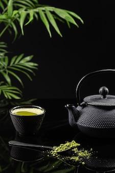 Matcha-teepulver und teezubehör auf schwarzem hintergrund. tee-zeremonie. traditionelles japanisches getränk. vertikales format.