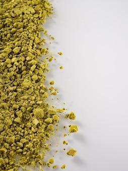 Matcha-teepulver von grüner farbe wird auf einem weißen hintergrund verstreut. platz kopieren.