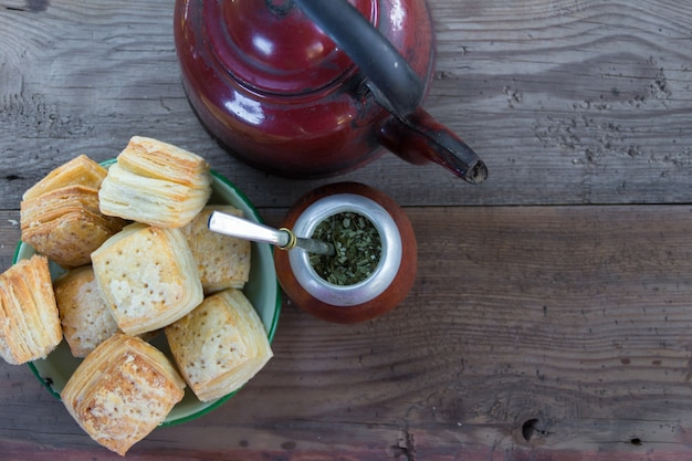 Mate und kessel mit einem teller mit salzigen argentinischen keksen und yerba mate infusion