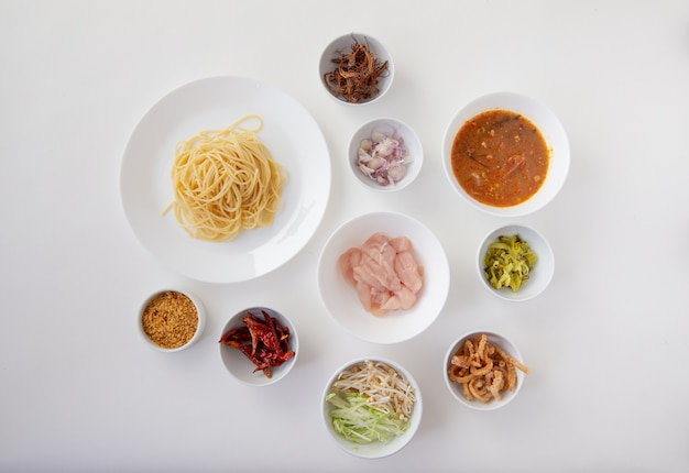 Material von würzigen spaghetti mit thailändischen reisnudeln mit würziger hühnersauce isoliert weiß