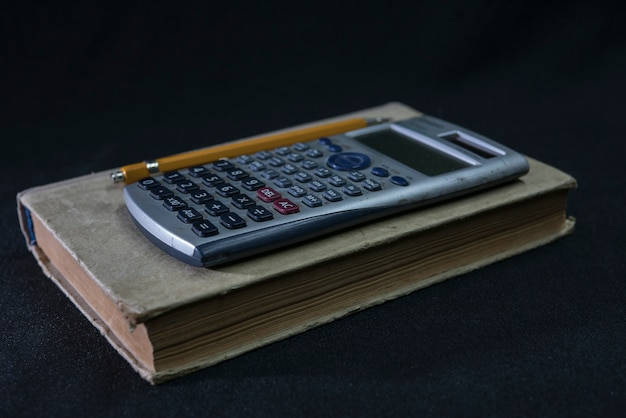 Mathe lehrbuch, bleistift und taschenrechner