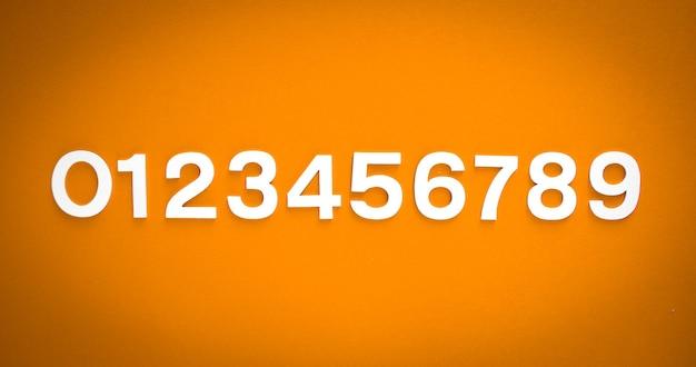 Mathematikhintergrund mit durchgehenden zahlen von 1 bis 9 auf einer orangefarbenen tafel